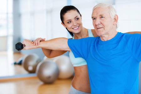 Usted está haciendo progreso! Fisioterapeuta femenino confidente que trabaja con el hombre mayor en el club de la salud Foto de archivo