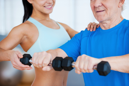 On the right way to recovery. Cropped image of female physical therapist helping senior man with fitness in health club photo