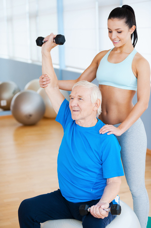 Just a little higher! Confident female physical therapist working with senior man in health club photo