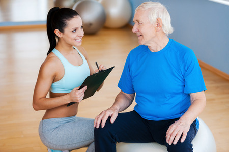 I will help you with your recovery. Confident physical therapist holding clipboard and smiling while sitting close to senior man photo