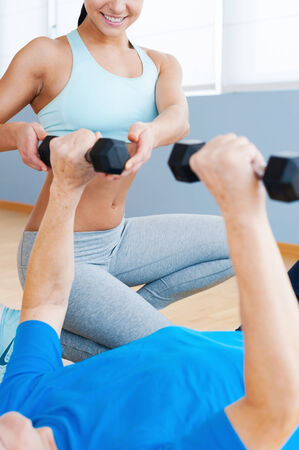 Supporting the all way to recovery. Cropped image of cheerful female personal coach supporting senior man in weight exercises photo