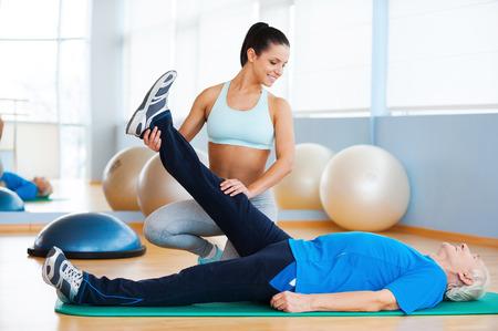 terapia ocupacional: Fisioterapia. Fisioterapeuta femenino confidente que trabaja con el hombre mayor en el club de la salud Foto de archivo