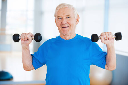 people  camera: Staying healthy. Happy senior man exercising with dumbbells and smiling while standing indoors