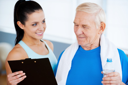 Great results! Confident personal coach standing close to senior man and showing something at her clipboard photo