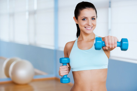 gym ball: Exercising with dumbbells. Beautiful young woman in sports clothing exercising with dumbbells and smiling while standing in health club Stock Photo