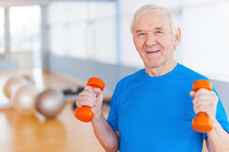 terapia ocupacional: En el camino hacia la recuperaci�n. Hombre mayor feliz ejercicio con pesas y sonriendo mientras est� de pie en el interior Foto de archivo