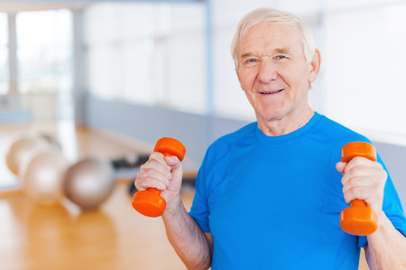 people exercising: On the road to recovery. Happy senior man exercising with dumbbells and smiling while standing indoors Stock Photo