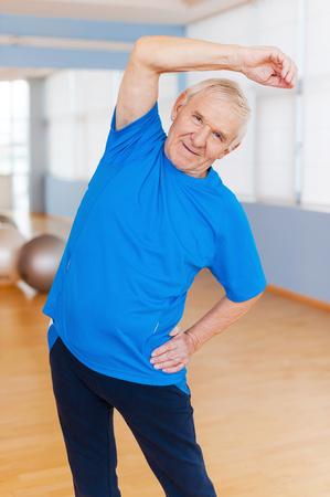 terapia ocupacional: Mantenerse activo. Hombre mayor alegre que hace ejercicios de estiramiento y sonriendo mientras est� de pie en el interior