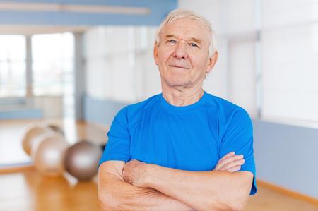 cuerpo hombre: Confiado y saludable. Confiamos en el hombre manteniendo altos los brazos cruzados y mirando a la c�mara mientras est� de pie en el gimnasio con equipamiento deportivo que se en el fondo Foto de archivo