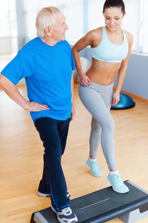 Doe het op deze manier. Volledige lengte van vrolijke fysiotherapeut werken met senior man in healthclub
