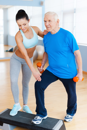 You can do it! Full length of confident female physical therapist working with senior man in health club photo
