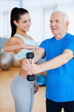 You are doing good! Confident female physical therapist helping senior man with fitness in health club photo
