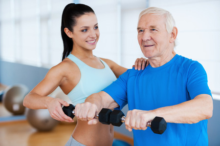 Next step to full recovery. Confident female physical therapist helping senior man with fitness in health club photo