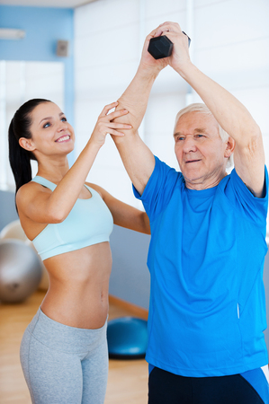 Progressing day by day. Cheerful female physical therapist helping senior man with fitness in health club photo