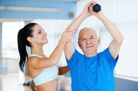 You are making great progress! Confident female physical therapist working with senior man in health club photo