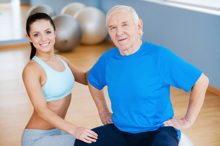 On the road to full recovery. Confident female physical therapist looking at camera and smiling while sitting close to cheerful senior man photo
