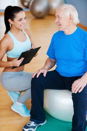 terapia ocupacional: Usted está haciendo un gran progreso. Entrenador personal confidente que sostiene el sujetapapeles y sonriendo mientras está sentado cerca de hombre mayor