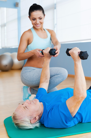 Progressing day by day. Confident female physical therapist supporting senior man in weight exercises photo