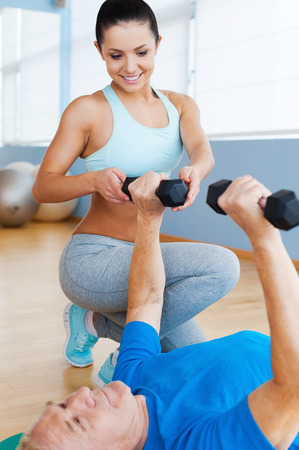 Supporting in every move. Confident female physical therapist supporting senior man in weight exercises photo
