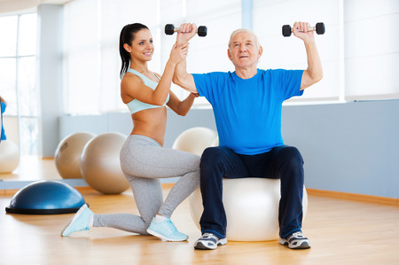 Weight exercises. Confident female physical therapist working with senior man in health club photo