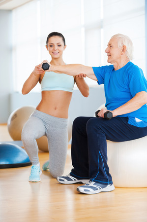 Helping to stay healthy. Confident female personal trainer helping senior man with weight exercise photo