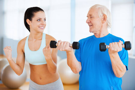 And three times more. Confident female physical therapist showing how to make weight exercise to senior man in health club photo