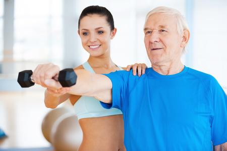 Usted está haciendo bien! Fisioterapeuta femenino alegre que ayuda al hombre mayor con la aptitud en el club de la salud