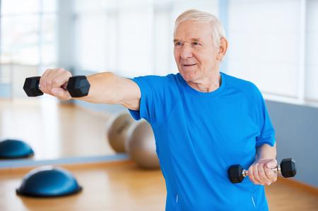 terapia ocupacional: Luchando con la edad. Hombre mayor confidente ejercicio con pesas y sonriendo mientras est� de pie en el club de la salud