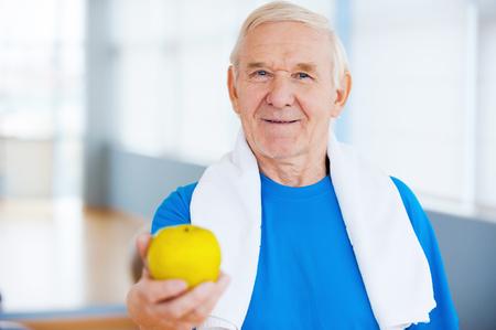 cuerpo hombre: �nete estilo de vida saludable! Hombre mayor feliz con una toalla sobre los hombros de estiramiento a cabo manzana verde mientras est� de pie en el club de la salud Foto de archivo