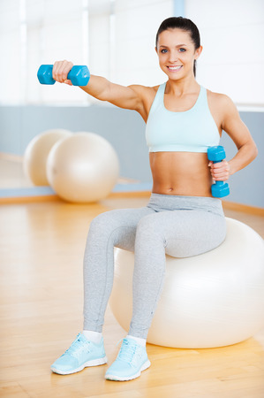 one person only: Keeping my body fit. Beautiful young woman in sports clothing exercising with dumbbells and smiling while sitting on fitness ball