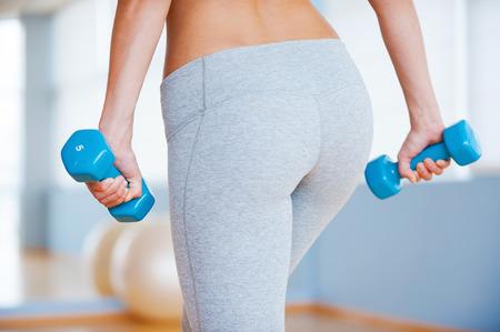 hintern: Perfekte Gesäß. Rückansicht sportliche Frau mit perfekten Hintern halten Hanteln im Stehen in Fitness-Club