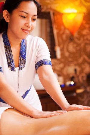Restablecer el equilibrio vida. Confía terapeuta de masaje tailandés masaje de espalda femenino y sonriente Foto de archivo - 33746223