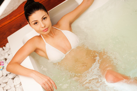 hot breast: Luxury bath. Top view of attractive young woman relaxing in hot tub and looking at camera Фото со стока