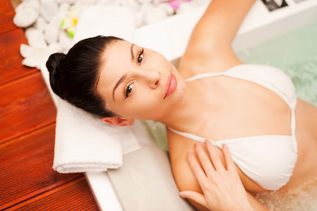 sex symbol: Spa treatment. Top view of beautiful young black hair woman relaxing in hot tub and touching her face