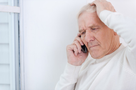 one senior man only: Having some troubles. Frustrated senior man talking on the mobile phone and touching his head while leaning at the wall Stock Photo