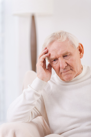 one senior man only: Felling lonely. Frustrated senior man touching his head while sitting in chair Stock Photo