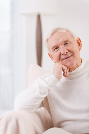 one senior man only: Feeling peaceful at home. Cheerful senior man holding hand on chin while sitting in chair Stock Photo