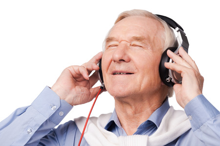 Listening to his favorite music. Portrait of cheerful senior man in headphones listening to music and keeping eyes closed while standing against white background photo