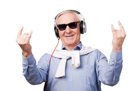 escucha activa: Joven para siempre. Hombre mayor alegre en los auriculares escuchando música y mostrando signo de la mano mientras está de pie contra el fondo blanco Foto de archivo