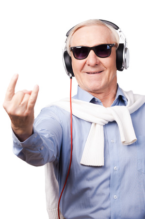 rock hand: Rock star. Cheerful senior man in headphones listening to music and showing hand sign while standing against white background Stock Photo
