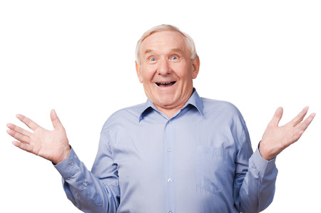 one man only: Can you believe that!  Excited senior man gesturing and smiling while standing against white background