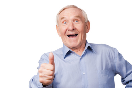 looking up: It is cool! Excited senior man stretching out his hand with thumb up while standing against white background