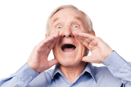Can you hear me?  Excited senior man shouting while standing against white background