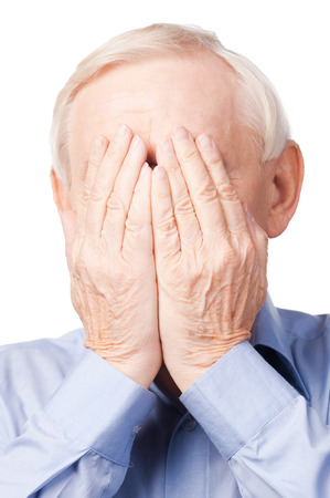 Oh my God!  Frustrated senior man covering his face by hands while standing against white