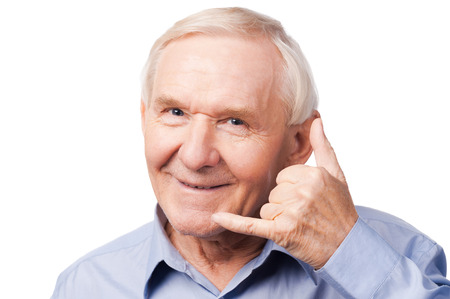Waiting for your call. Cheerful senior man in shirt gesturing mobile phone near his face and smiling while standing against white background