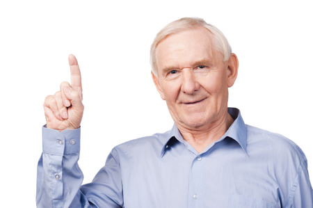 one senior man only: Look over there! Cheerful senior man pointing up and smiling while standing against white background