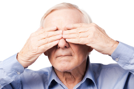 hands covering eyes: I did not see anything. Frustrated senior man covering his eyes by hands while standing against white background Stock Photo