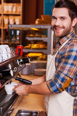 making love: I love my job. Handsome male barista making coffee and smiling while standing at the bar counter near the coffee machine