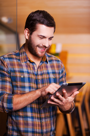 surfing the net: Man surfing the net. Handsome young man working on digital tablet and smiling while standing indoors