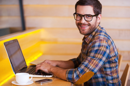 smiling man: Enjoying free WiFi in cafe. Handsome young man working on laptop and smiling while sitting in cafe Stock Photo